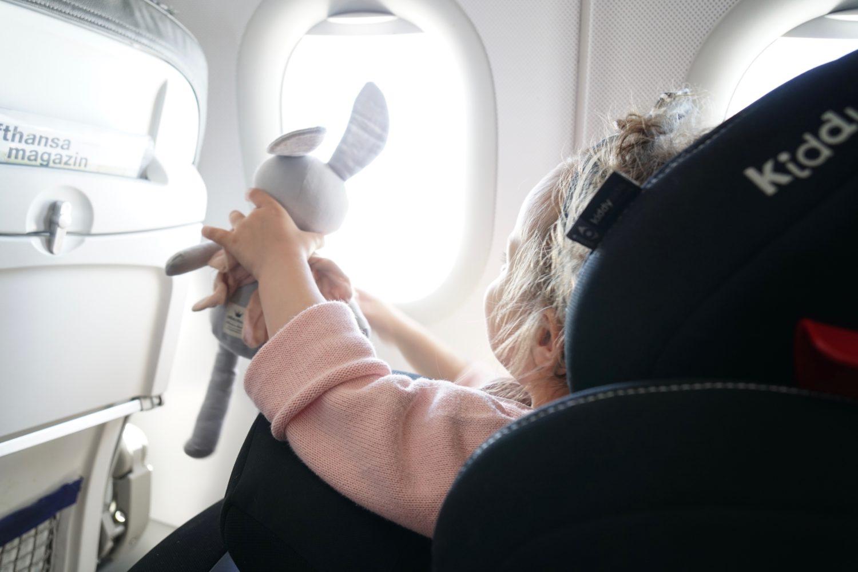 Minnie sitzt auf ihrem Kindersitz im Flugzeug und zeigt ihrem Hase die Wolken