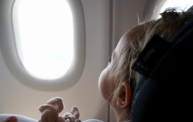 Minnie sitzt auf ihrem Kindersitz im Flugzeug und schaut raus.
