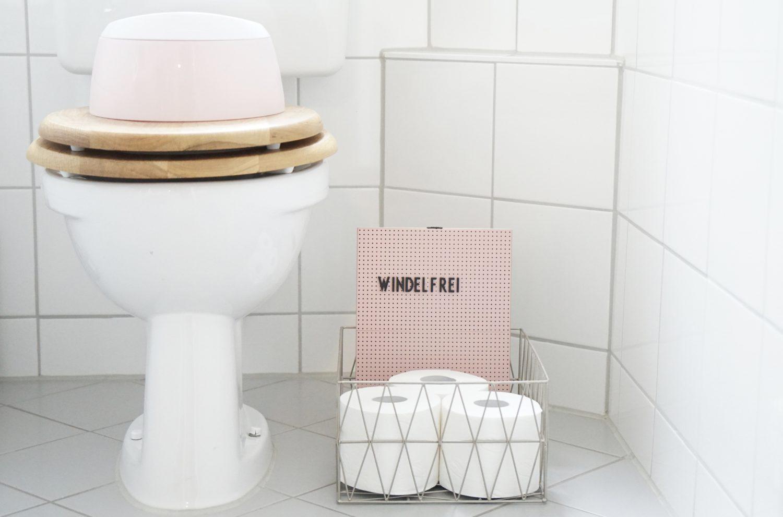 Windelfrei - Töpfchen auf der Toilette stehend und Toilettenrollen