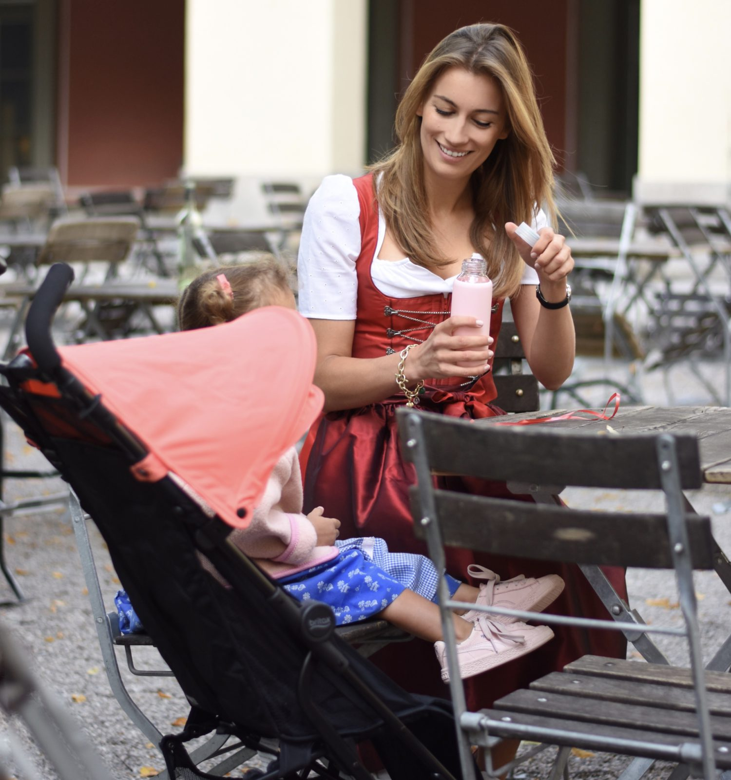 Wiesn mit Kind - Mama und Tochter sitzen gemeinsam am Biergartentisch.
