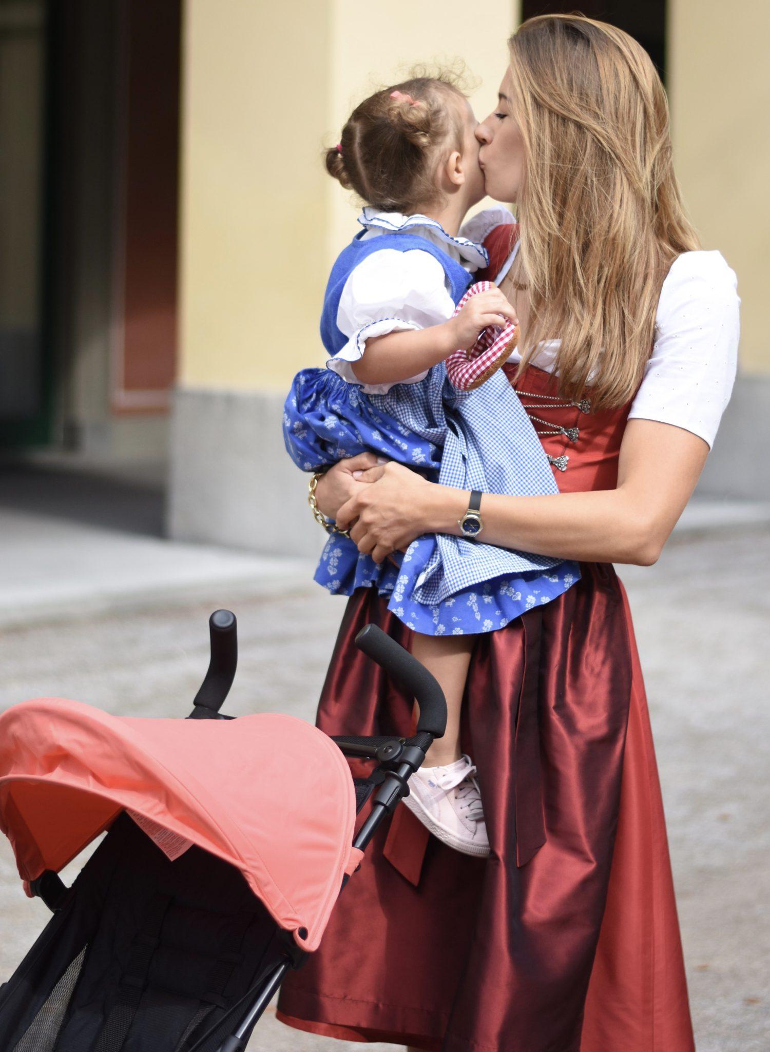 Wiesn mit Kind - Mama hält Tochter auf dem Arm, küsst sie und davor steht der Biggy HOLIDAY von Britax Römer.