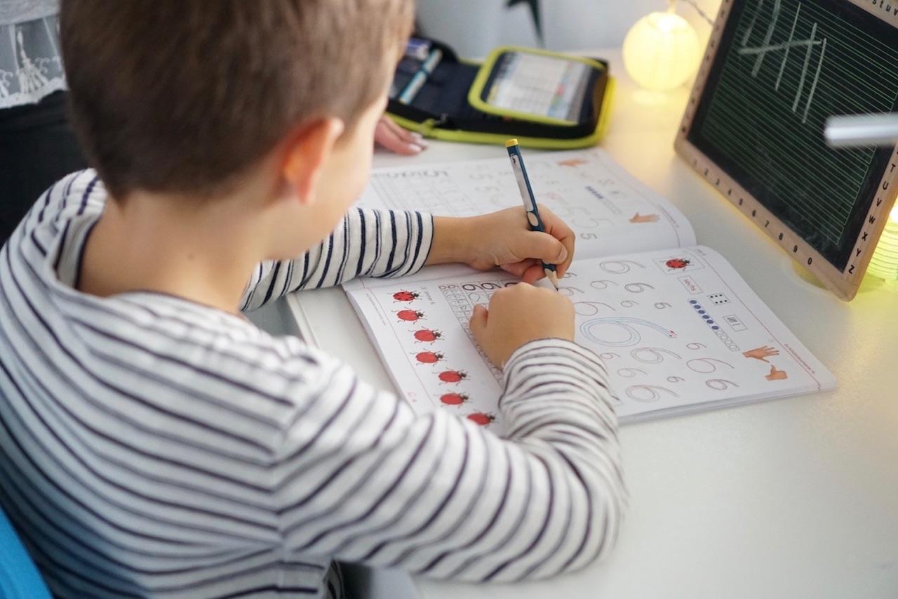 Mein Schulkind übt Zahlen zu schreiben.