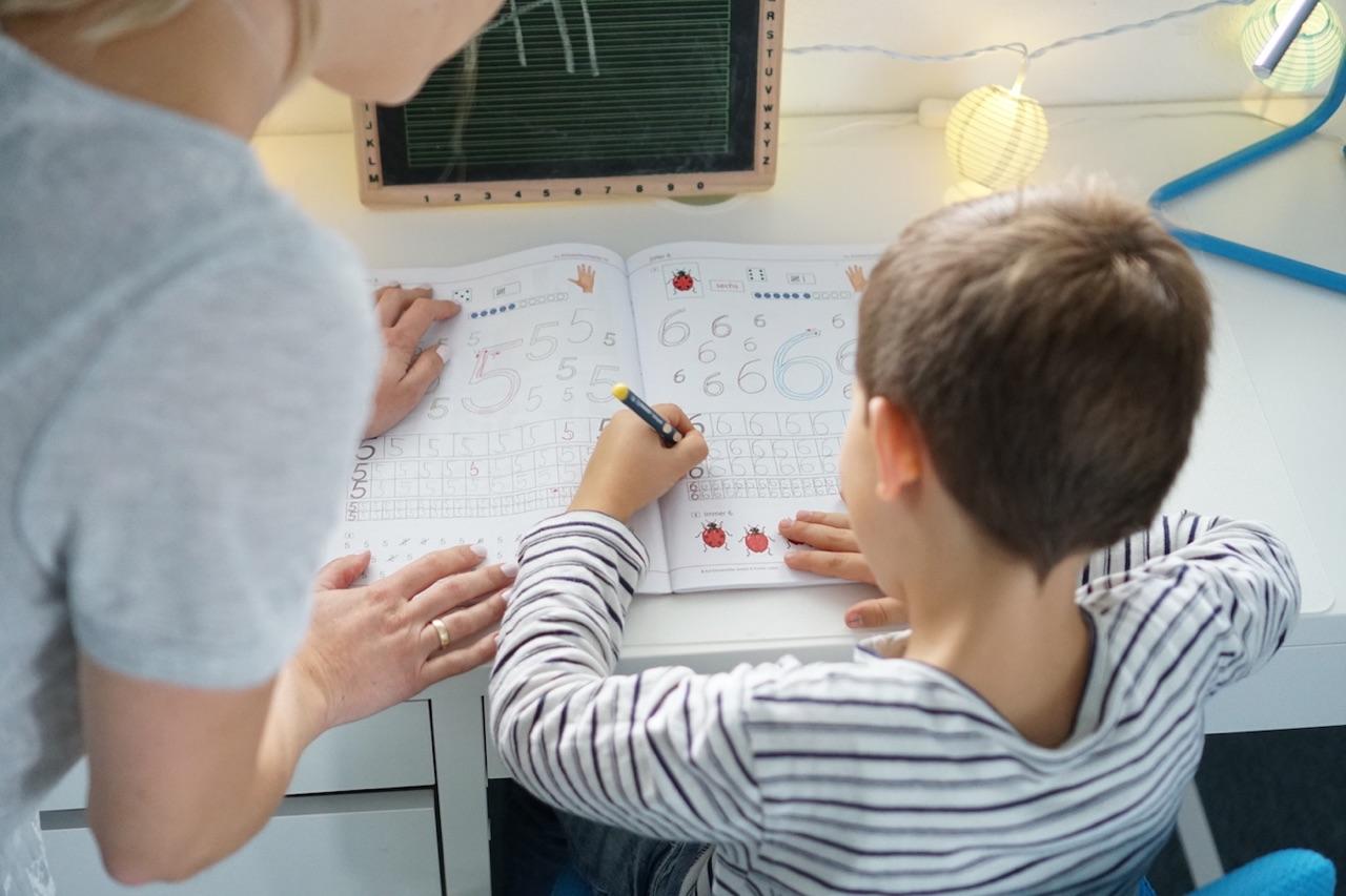 Mama stärkt dem Schulkind den Rücken beim Schulaufgaben machen.