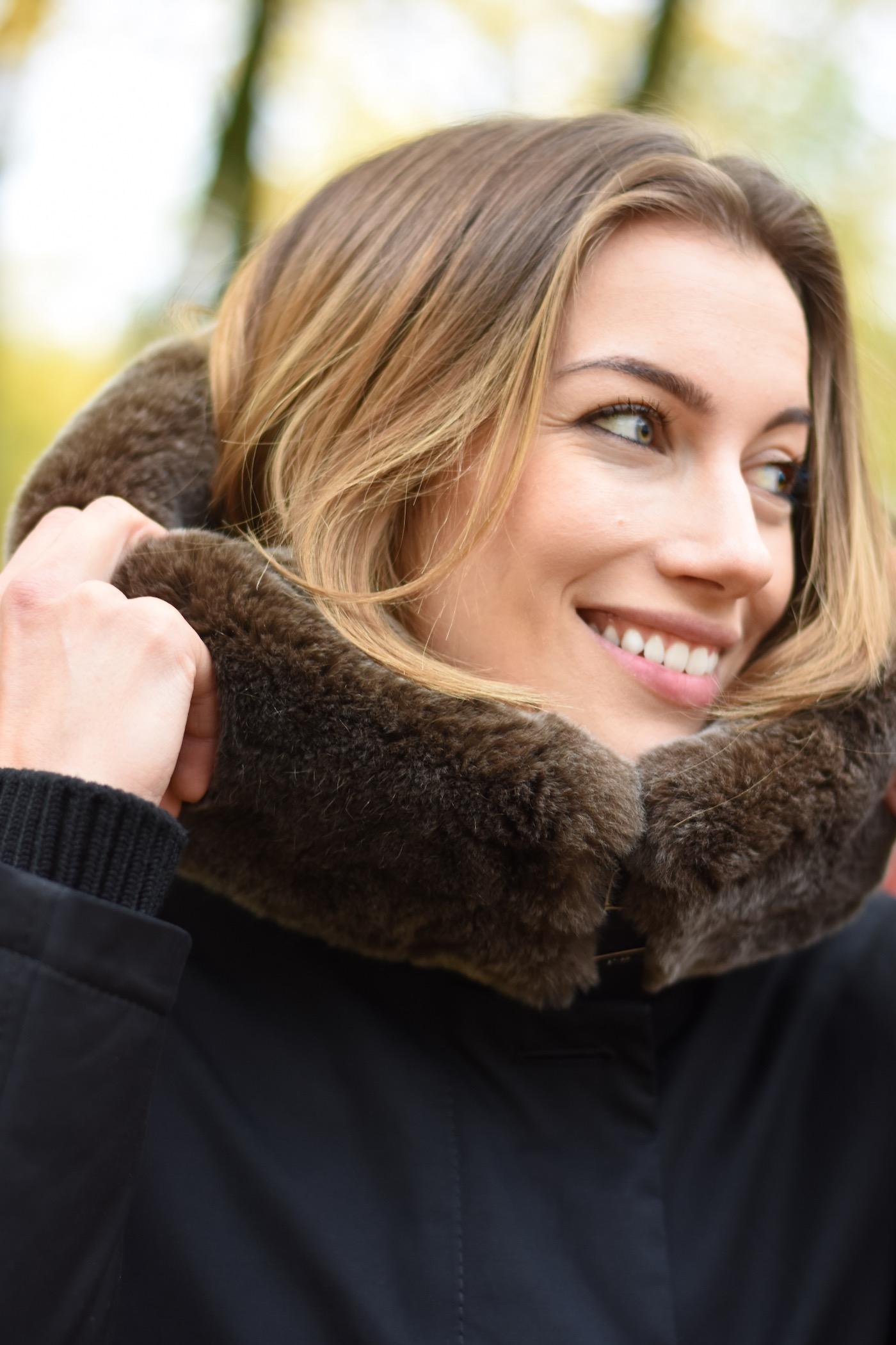 Susanna hält den Kragen der Jacke und lächelt zur Seite.